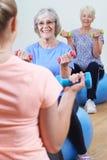 Старшие женщины на классе фитнеса с инструктором Стоковые Изображения