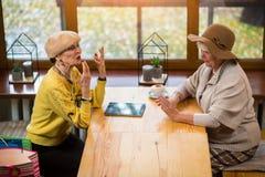 Старшие женщины на таблице кафа Стоковые Фотографии RF