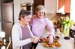 Старшие женщины подготавливая еду в кухне стоковые изображения rf