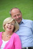 Старшие кавказские пары смеясь над совместно outdoors Стоковые Фотографии RF