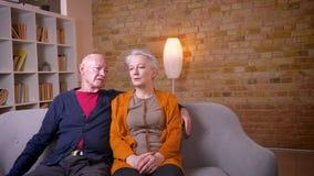 Старшие кавказские супруги сидя совместно на софе прижимаясь и разговаривая с другой быть счастливый дома видеоматериал