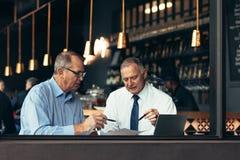 Старшие люди обсуждая деловой документ в кафе стоковое фото