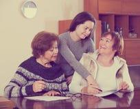 Старшие милые усмехаясь женщины делая будут на нотариальной конторе стоковая фотография rf