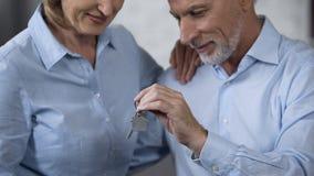 Старшие мужские ключи дома удерживания, дама усмехаясь, вклад приобретения недвижимости стоковые фото