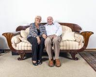 Старшие пары в влюбленности сидя на софе Стоковая Фотография