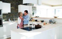 Старшие пары в кухне варя и танцуя совместно Стоковые Фотографии RF