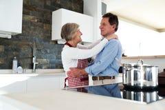 Старшие пары в кухне варя и танцуя совместно Стоковое Изображение RF