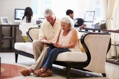 Старшие пары в лобби гостиницы смотря таблетку цифров Стоковое фото RF