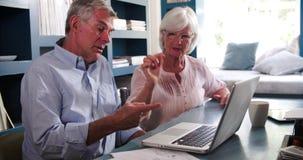 Старшие пары в домашнем офисе смотря компьтер-книжку и спорить сток-видео