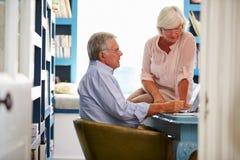 Старшие пары в домашнем офисе смотря компьтер-книжку Стоковые Фотографии RF