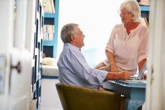 Старшие пары в домашнем офисе смотря компьтер-книжку Стоковое фото RF