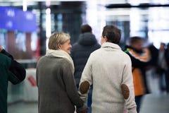 Старшие пары в прихожей метро, держа руки изолированная белизна вид сзади Стоковые Фото
