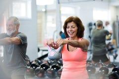 Старшие пары в спортзале разрабатывая используя kettlebells Стоковые Фото