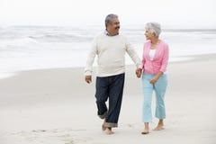 Старшие пары гуляя вдоль пляжа совместно Стоковая Фотография