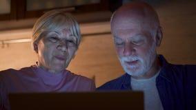 Старшие пары дома используют компьтер-книжку в кухне на ноче Выбытая семья работы пенсионеров на компьютере видеоматериал