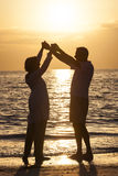 Старшие пары держа пляж захода солнца рук тропический Стоковое Фото