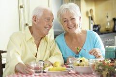 Старшие пары есть еду совместно в кухне стоковая фотография
