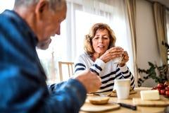 Старшие пары есть завтрак дома Стоковые Изображения RF