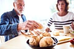 Старшие пары есть завтрак дома Стоковая Фотография RF