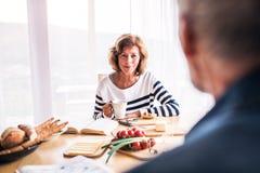 Старшие пары есть завтрак дома Стоковое фото RF