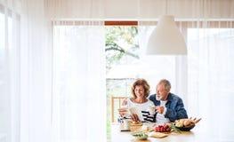Старшие пары есть завтрак дома Стоковая Фотография