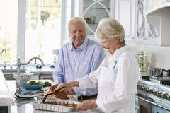 Старшие пары делают еду Турции жаркого в кухне совместно Стоковые Фото