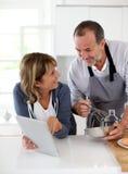 Старшие пары делая печенья в кухне стоковая фотография