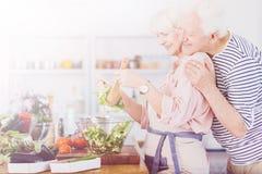 Старшие пары делая салат стоковые фото