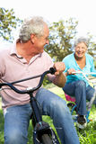 Старшие пары играя на bikes детей Стоковые Фотографии RF