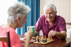 Старшие пары играя шахмат стоковые фото