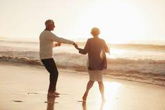 Старшие пары имея потеху на пляже Стоковые Фото