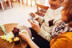 Старшие пары используя телефон в кафе Выбытые люди учат как использовать новые technolodies Семья ослабляет в кафе Стоковые Фотографии RF