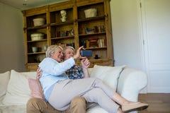Старшие пары используя мобильный телефон Стоковые Изображения RF