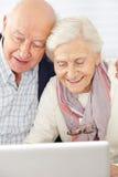 Старшие пары используя социальные средства массовой информации стоковые фото