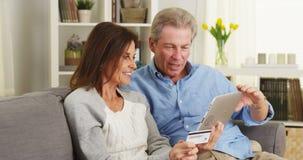 Старшие пары используя таблетку для того чтобы сделать приобретение стоковое изображение rf