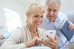 Старшие пары используя smartphone дома Стоковое Фото