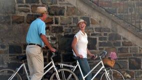 Старшие пары идя на велосипед едут в городе видеоматериал