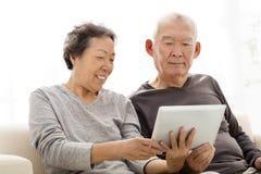Старшие пары наблюдая таблетку на софе стоковые изображения rf