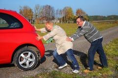 Старшие пары нажимают сломленный автомобиль стоковая фотография