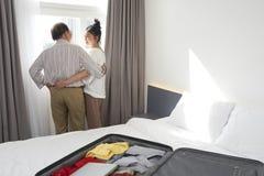 Старшие пары наслаждаясь взглядом из окна гостиницы стоковое изображение rf