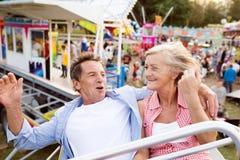 Старшие пары на езде в парке атракционов стоковое фото rf