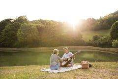Старшие пары на озере имея пикник Стоковое фото RF