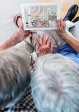 старшие пары на софе с таблеткой (взгляд сверху) На таблетке дизайн новой комнаты (цвета: зеленый цвет, Стоковое Фото