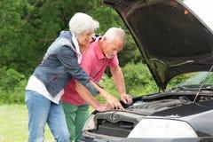 Старшие пары на сломленном автомобиле Стоковая Фотография