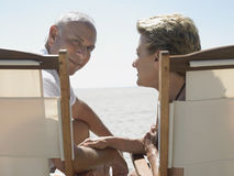 Старшие пары на Deckchairs на пляже Стоковое фото RF