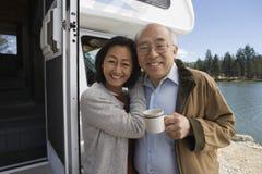 Старшие пары обнимая снаружи RV на озере стоковые изображения