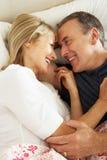 Старшие пары ослабляя совместно в кровати Стоковое Фото