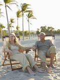Старшие пары ослабляя на Deckchairs на пляже Стоковое Фото