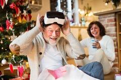 Старшие пары перед рождественской елкой с изумлёнными взглядами VR Стоковое Фото