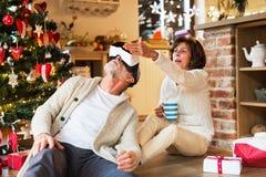 Старшие пары перед рождественской елкой с изумлёнными взглядами VR Стоковое фото RF